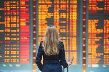 Frau an internationalem Flughafen for Abflugstafel - educom bietet Sprachkurse inn über 50 Sprachen