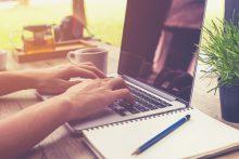 person tippt auf Laptop mit Geschäftsunterlagen