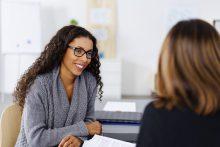 Zwei Frauen unterhalten sich am Tisch - educom bietet fachspezifische Sprachkurse