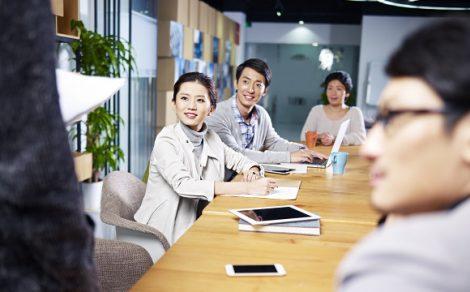 Asiatische Geschäftsleute sitzen am Tisch - Interkulturelle Trainings bei educom