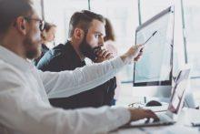 Geschäftsmänner besprechen sich an Bildschirm