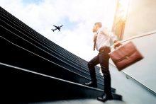 Mann auf Treppe, Flugzeug am Himmel