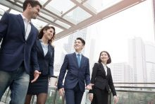 Lockere internationale Geschäftsbesprechung vor Hong Kong Skyline