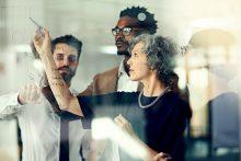 Teambesprechung mit Ideen und Skizzen an der Glaswand - educom bietet Sprachkurse für Marketing Englisch, alle Sprachen