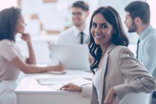 Lächelnde Geschäftsfrau an Besprechungstisch - Sprachkurs HR-Englisch bei educom
